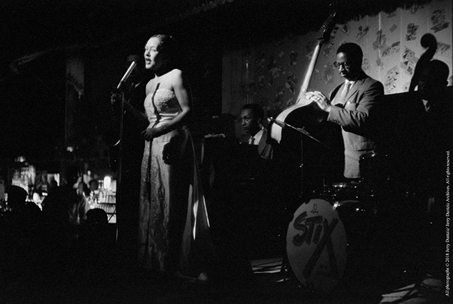 Billie Holiday performing on stage with her band - Paul Quinichette on tenor saxophone Carl Drin